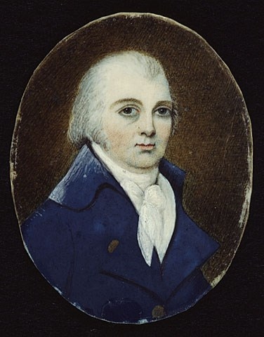 portrait of an old white haired man witha small, round, pale face and sharp blue jacket. he has big round dark eyes