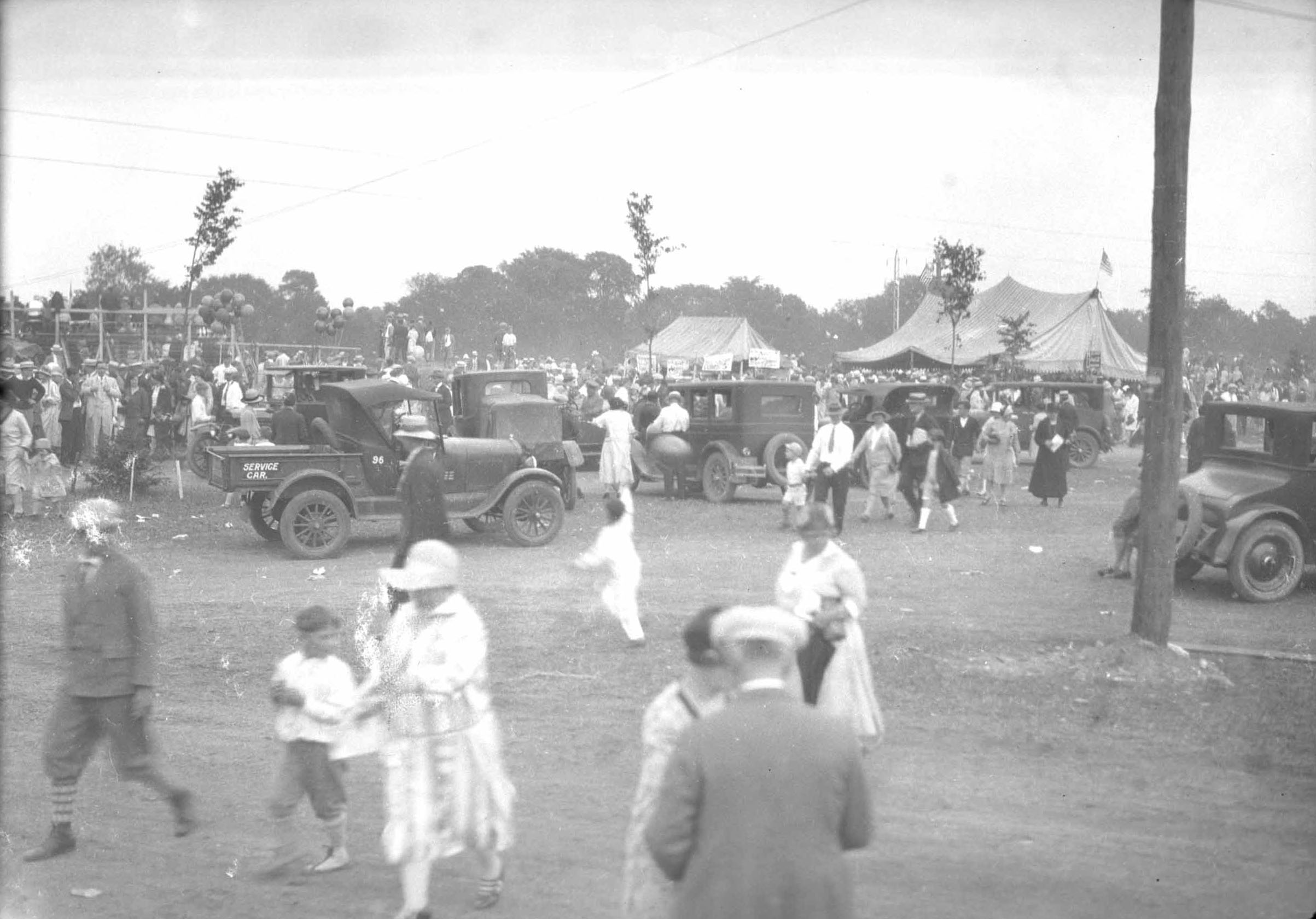 1920's era picture, an area busy with  tents, hussel  and bussel, people are observing displays.