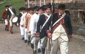 Soldiers march in file. All wear woolen jackets or white linen shirts, and large black hats. Everyone carries a musket.