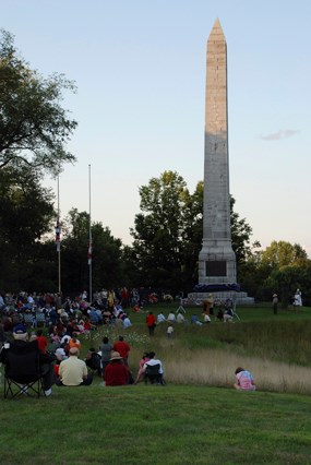 A white stone obelisk in shadow, people sit in a grassy green field surrounding, they are all shapes and colors