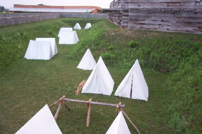 a grassy green area with white tents dot the edges of the forts walls