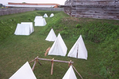a lush green grassy hole is filled with large, white, triangular, canvas tents. wooden walls and shadows loom over them.