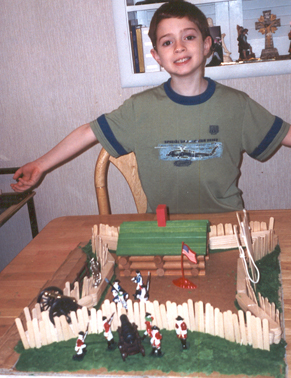 a boy with a green shirt opens his arms and smiles wide. he is showing the camera a model fort that was made by hand!
