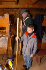 a child in a winter jacket stands in a soldier's barracks and passes wooden muskets from a continental soldier to other kids