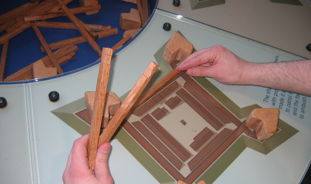 a glass tabletop with hands holding wooden blocks. they are constructing a building