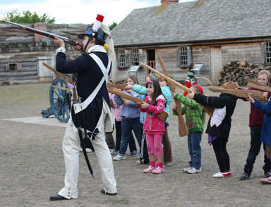 a soldier in a tall hat directs young girls how to stand in a postion of a soldier while holding a musket. all are in a neat row