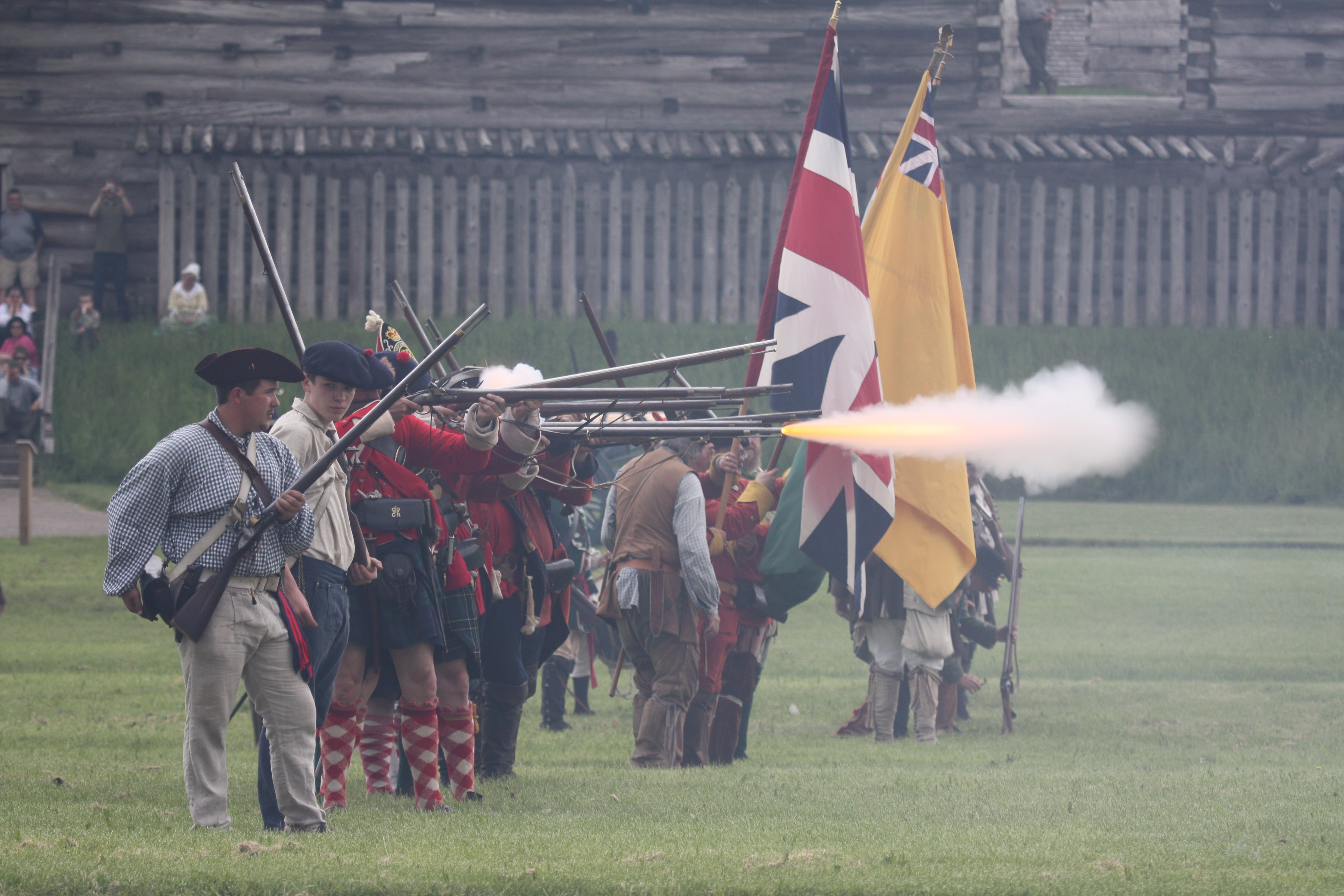 Soliders march in a line with a multi-colored flags. Smoke billows in from of them, pouring from muskets.