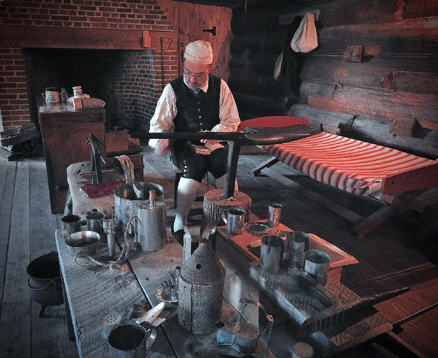 A man in 18th century clothing sits with an anvil in front of him. It is a large black piece of metal. On that he hammers a shiny piece of silver gently.