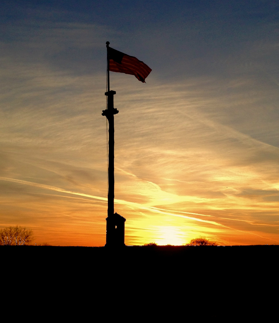 A flag waves in a vivid orange sunset over a shadowed wooden wall.