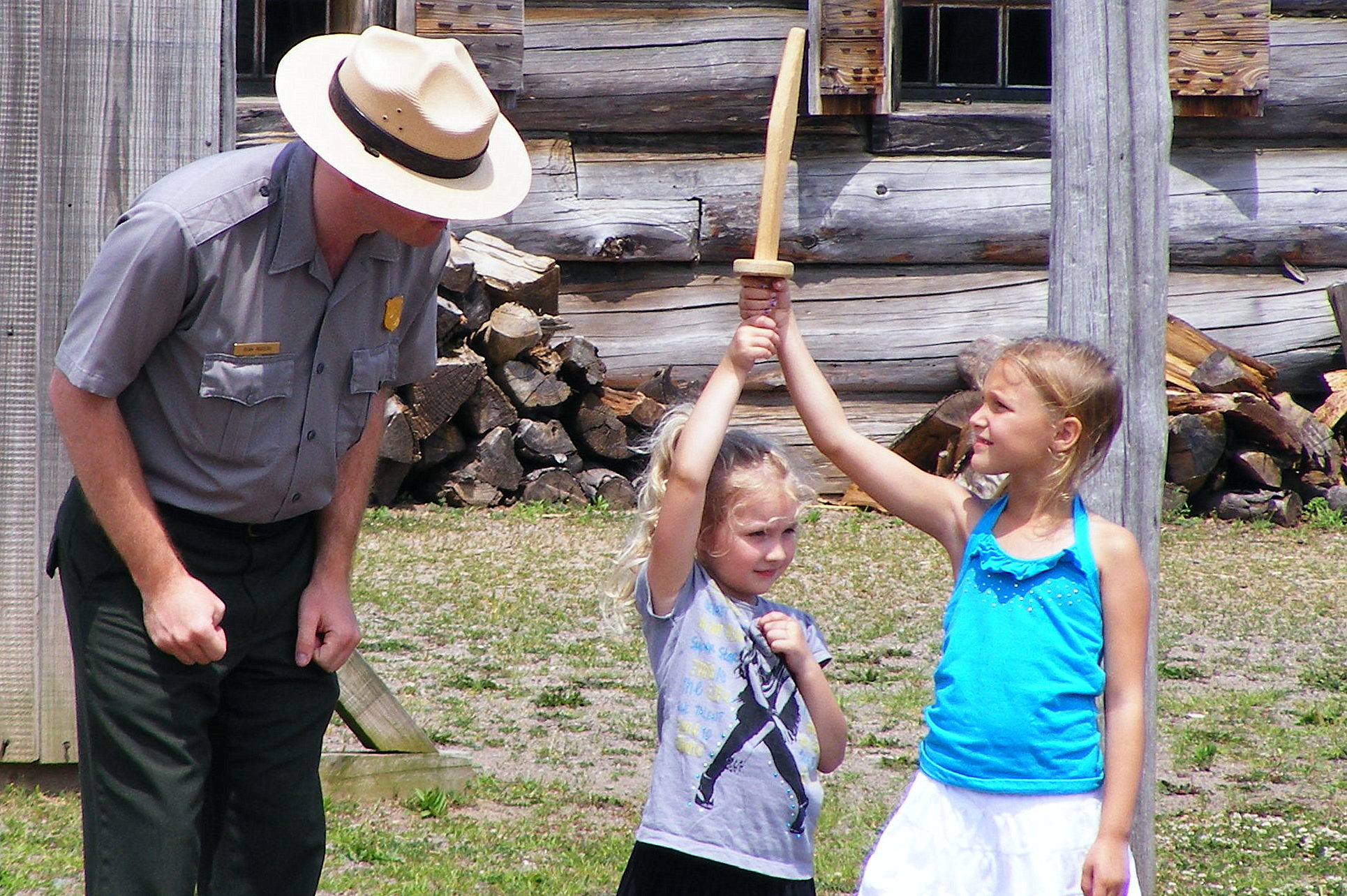 A little girl and her sister hold a wooden sword next to a park ranger.