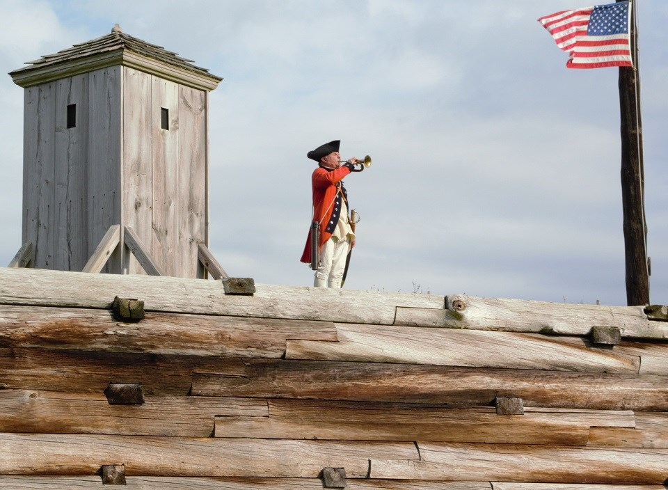A man in a bright red jacket stands on a wooden wall playing a bugle.