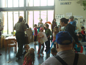a busy foyer with children rushing about. they carry papers of many colors. A park ranger directs them