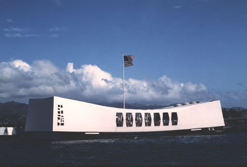 a curved large white box with windows sits on top of the ocean. a US flag flys above.
