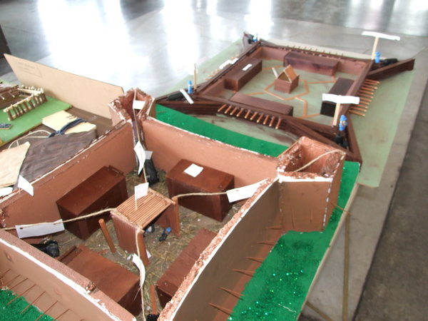 a sturdy brown cardboard model of forts with a green backing sits on a table. string ties crucial pieces together and labels them