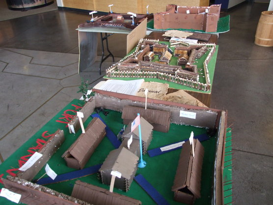 carefully constructed models of forts in brown cardboard and wood sit on tables with little white labels attached to different pieces