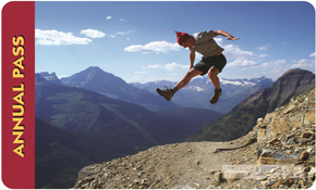 Federal Lands Pass 2012: a man jumps from a mountain cliff and seems to pause against a blue silouette of peaks