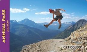 A man jumps from a mountain cliff and seems to pause against a blue silouette of peaks