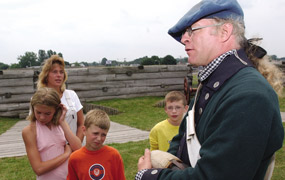 A tall soldier wears a green woolen jacket, he is speaking to children in multicolored tee-shirts on a corner of the fort.
