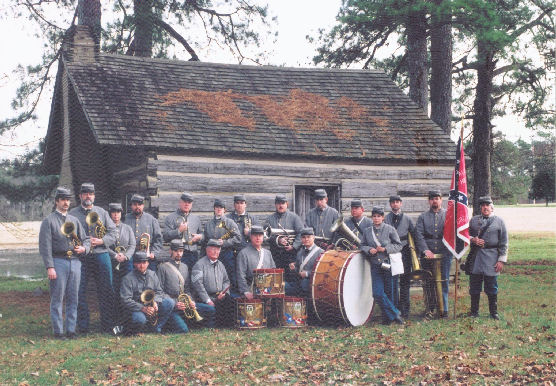 Members of the 8th Georgia Band pose in front of a log cabin in Danville, Kentucky