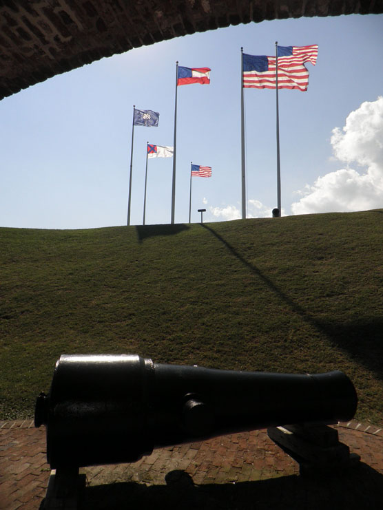 A Civil War cannon with the U.S. flag and five historic flags of Fort Sumter flying in the distance.