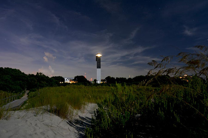The Sullivan's Island Lighthouse with its light shining as viewed from the beach