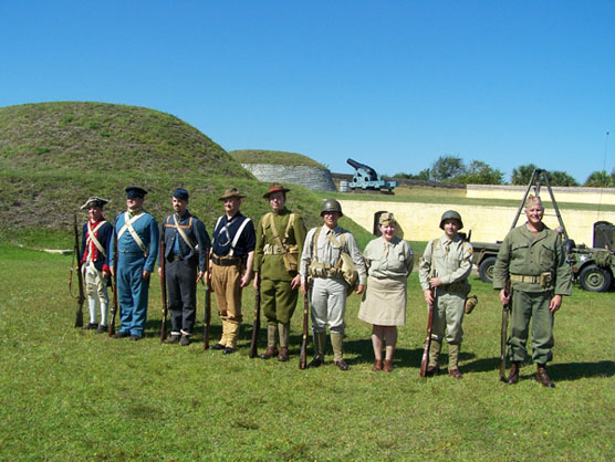 Nine people dressed as soldiers from the Revolutionary War through WWII.