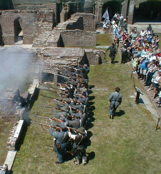 A line of Civil War reenactors fire muskets while visitors watch.