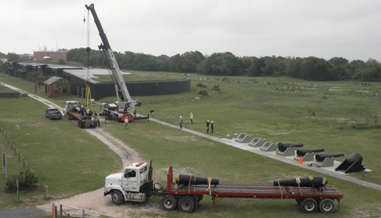 Large cannons are lifted by heavy crane and placed on flatbed trucks.