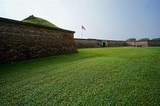 Fort Moultrie's stone walls surrounded by green grass against a blue sky.