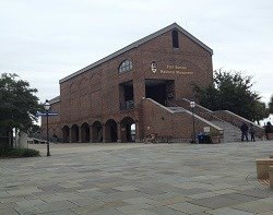 Large brick building with a paved courtyard against blue sky