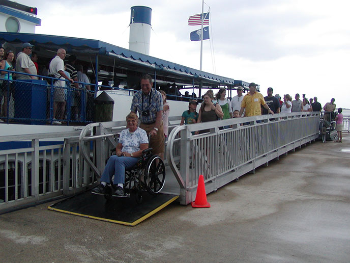 A visitor in a wheelchair descends the ramp from the boat to the Fort Sumter dock.