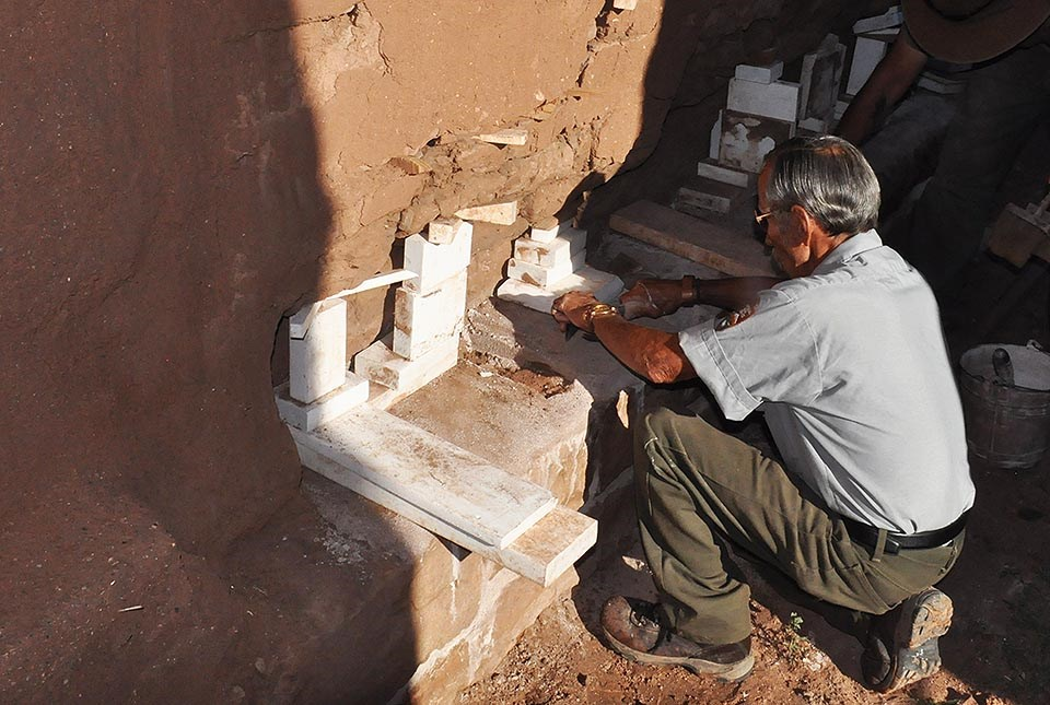A member of the Fort Union preservation crew works on an adobe wall.