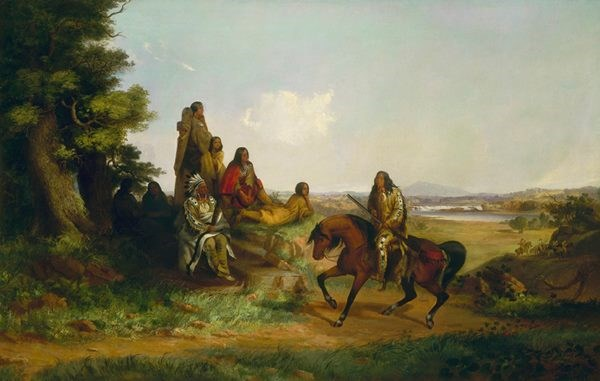 Group of American Indians, one man on horseback with long gun, one woman standing with cradle board and baby, rest seated in foreground of western landscape.