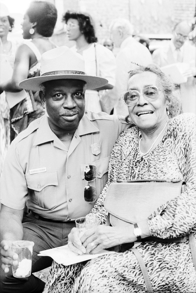 African American Park Ranger with African American Woman in dress smiling at camera durring opening ceremony.