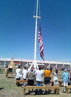 Flag raising on new flagpole, visitors standing