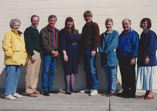 Eight people standing facing the camera smiling.