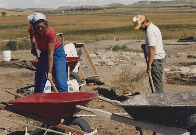 A woman and a man working the archaeological digs with shovels and wheelbarrows. A Woman, in red shirt, blue jeans, sunglasses and headscarf. A man in a baseball hat, white shirt and green dungarees.