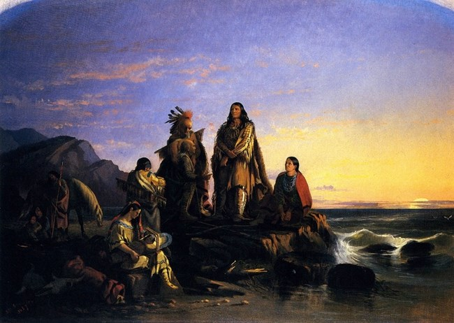 Group of American Indians in foreground of mountain/ocean background