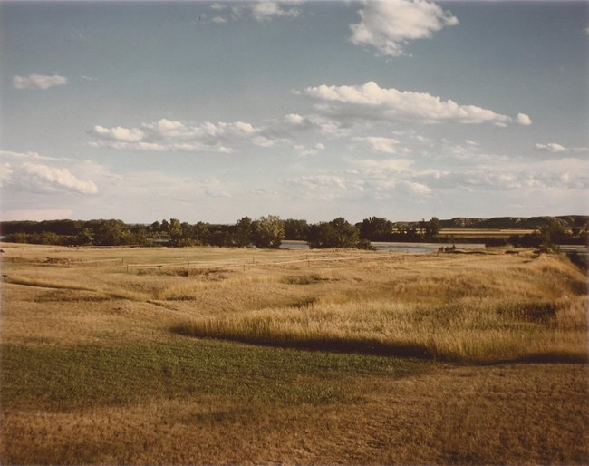 Open grassy plain, Missouri River is visible in the background.
