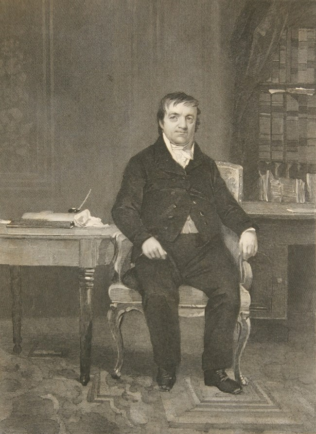Black and white image of a man in formal 1800s suit sitting in a library setting