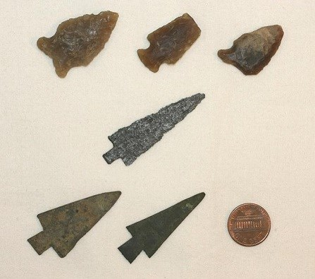 Three brown flint stone and three metal arrowheads.