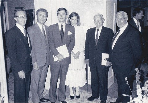 Five men in suits and one women in a dress pose for a photograph.