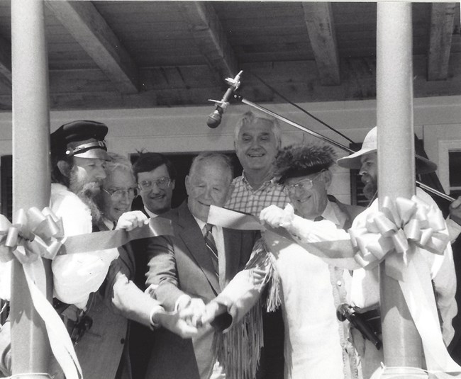 Seven men stand on the Bourgeois House porch and cut the ceremonial ribbon opening Fort Union to the public.