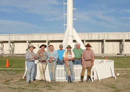Men pose in front of installed flagpole and flagpole fence.