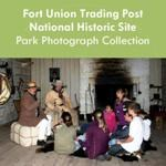 Two rangers in historic clothing talk to a group of school age children