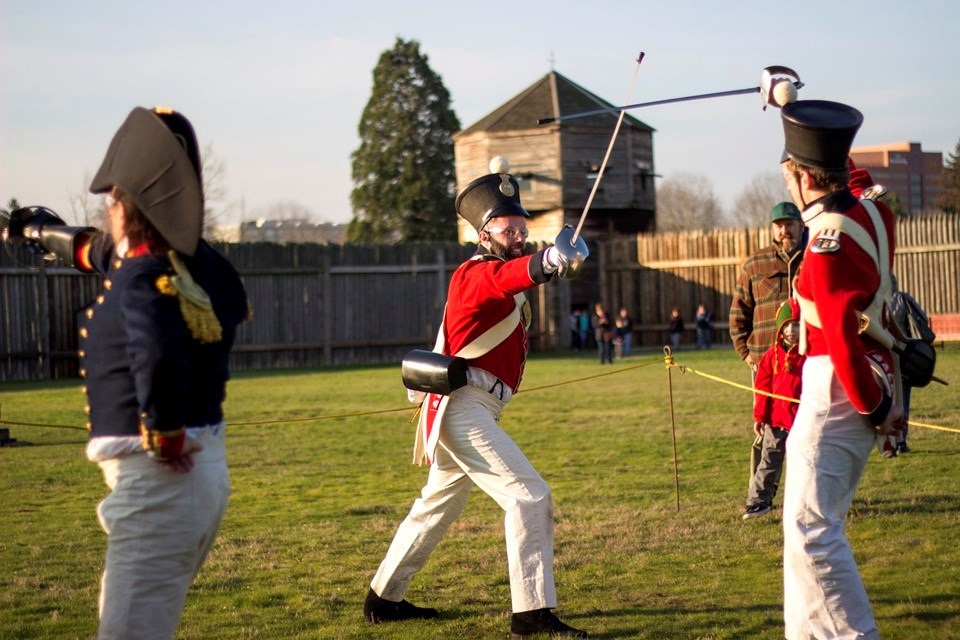 Photo of two reenactors in historic military costume inside the fort demonstrating saber techniques.