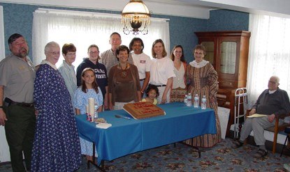 Image of staff and volunteers standing around a cake commemorating the McLoughlin House Site's third anniversary