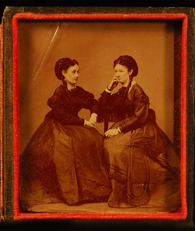 Sepia toned photograph of two women seated in a photography studio in the late 19th century.