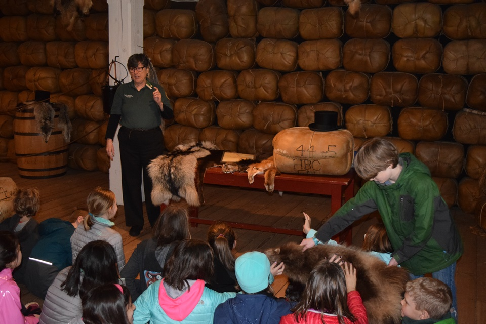 Students listen to a presentation about the fort's Fur Store