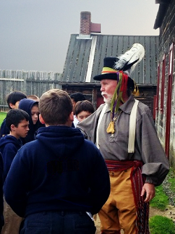 A former educator and Fort Vancouver volunteer teaches school kid about the Hudson Bay Trade Shop.